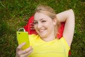 Garota exploração celular e ouvir música com fone de ouvido branco — Foto Stock