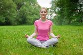 Blonde girl outdoor in the park wearing pink t-shirt. yoga — Stock Photo
