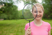 Blonde girl holding tennis -racket wearing pinck t-shirt — Stock Photo