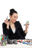 Brunette businesswoman putting on her make-up at work — Stok fotoğraf