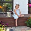 Little girl sitting on the porch with a watering can — Foto Stock