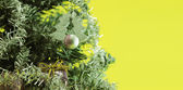 Christmas tree with decorations on yellow background — Stock Photo