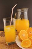 Glass and jug of orange soda — Stock Photo
