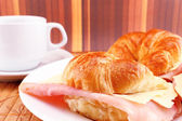 Coffee with croissants with ham and cheese — Stock Photo