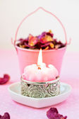 Beautiful spa setting with pink candle and rose petals. — Stock Photo