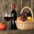 Still-life. Bottle of red wine, glass and basket with fruit — Stock Photo