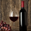 Still-life. Bottle of red wine, glass and grapes — Stockfoto