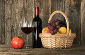 Still-life. Bottle of red wine, glass and basket with fruit — Stockfoto