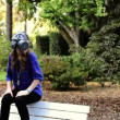 Stock Video: Nuclear war. Girl in gas mask sitting on bench