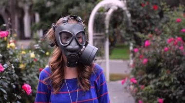 Girl in gas masks smells flowers — Stock Video
