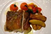 脆皮乳猪猪 rustico 烤土豆,青椒,炖的西红柿和蒜和迷迭香调味汁 — 图库照片