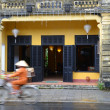 Local Cyclist in non la traditional hat against French colonial architecture in Hoi An, Vietnam — Stock Photo #40705953