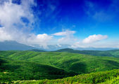 Mountain hills and bright sky with clouds. — Stock Photo