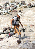 Tourist passes turbulent river — Stock Photo