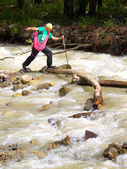 Tourist passes turbulent river. — Stock Photo