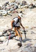 Tourist passes turbulent river. — Stock Photo