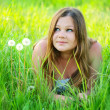 Dreamy woman lying on green grass — Stock Photo