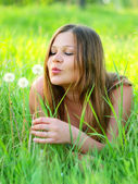 Nice girl laying down on the green grass with dandelion. — Foto Stock