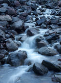 River among dark stones — Stock Photo