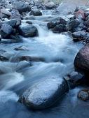 Río rápido entre piedras oscuras — Foto de Stock