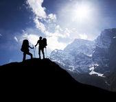 Silhouette of team on mountain peak — Stockfoto