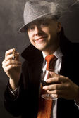 Happy businessman with drink and cigar — Stock Photo