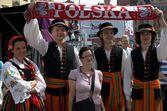 Football fan and folk dancers — Stock Photo