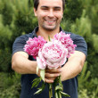 Man with flowers peony — Stock Photo