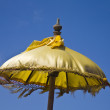 Stock Photo: Balinese ceremonial pajeng (umbrella) against blue sky