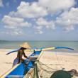 Fisher with fishing boat in Jimbaran bay, Bali - Stock Photo