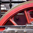 Close up of the red steel wheel of a classic steam locomotive - Stock Photo