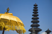 Balinese ceremonial pajeng (umbrella) with pura (temple) in the background — Stockfoto