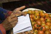 расчете на рынке продавец помидор — Стоковое фото