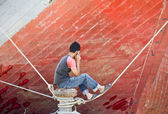 Asian man on the phone in front of the bow of a schooner — Stock Photo