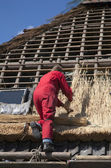 Workman thatching a new roof — Stock Photo