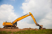 Excavator building a dike — Stock Photo