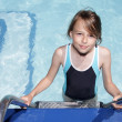 Girl on a ladder going into a swimmingpool — Stock Photo