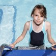 Stock Photo: Girl on a ladder going into a swimmingpool