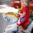 Stock Photo: Girl riding carousell horse