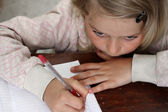 A little girl doing her homework — Stockfoto