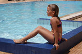 Young girl sitting by the pool — 图库照片