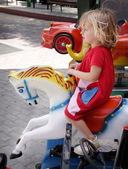 Girl riding a carousell horse — Stock Photo