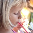 Girl drinking with straw — Stock Photo