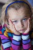 Sulky little girl with head in hands — Stock Photo