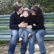 Asian mother caucasian father and child on a parkbench — Stock Photo