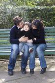 кавказский азиатских мать отец и ребенок на parkbench — Стоковое фото