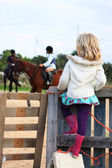 Girl watching a riding lesson — Stock Photo