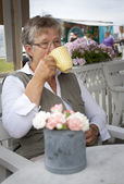 Old woman drinking coffee — Stock Photo