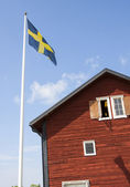Old Swedish wooden house with flagpole — Stock Photo