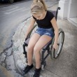 Stock Photo: Person in wheelchair trying to cross road